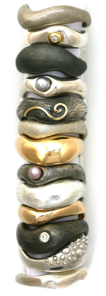Fed & Lækker ringe lignet op på række. Designet er inspireret af strandstenenes bløde organiske form, der ligger tæt op ad hinanden. Håndlavet hos Christel Kaaber Guldsmedie.