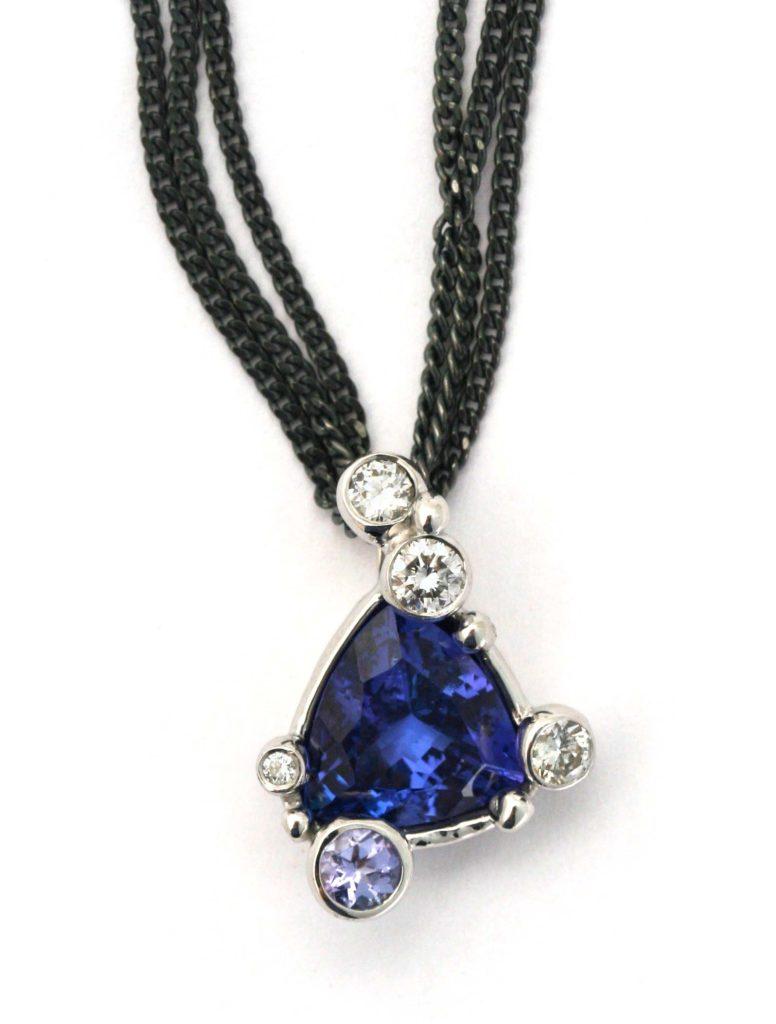 Detalje billede af vedhænget på halskæden. Den flotte meget blå tanzanite i midten, med den lyse blå tanzanit placeret under og brillanter omkring.