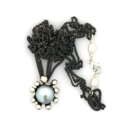 Halskæde vedhæng, der ligner en søanemone med en grå perle, samt perledetalje ved låsen. Håndlavet af Christel Kaaber Guldsmedie