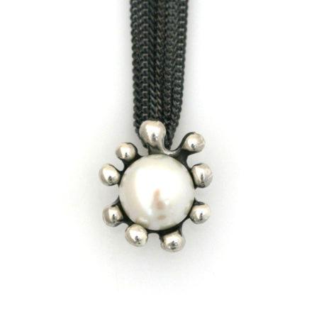 Halskæde med søanemone vedhæng og hvid perle i sorte kæder. Håndlavet af Christel Kaaber Guldsmedie