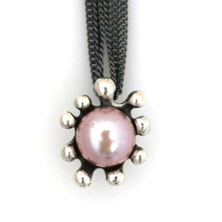 Close up af lang halskæde med søanemone vedhæng med rosa perle. Håndlavet af Christel Kaaber Guldsmedie