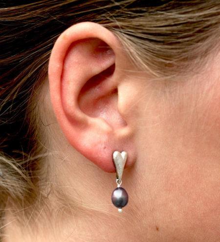 Flotte øreringe i sølv med hjertemotiv og mørk perle. Her set på mode. af Christle Kaaber Guldsmedie