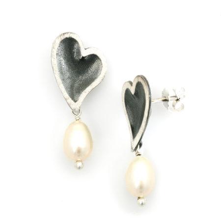 Hjertebue ørestik set i profil med en hvid perle hængende under. Håndlavet af Christel Kaaber Guldsmedie