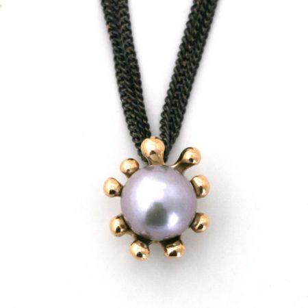 Søanemone halskæde i guld med grå perle set tæt på vedhænget med front. Designet og lavet af Christel Kaaber Guldsmedie