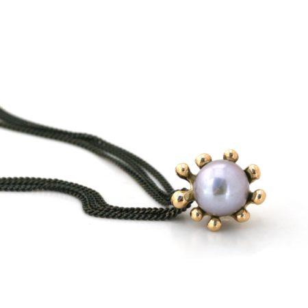 Søanemone halskæde i guld med grå perle set liggende. Håndlavet af Christel Kaaber Guldsmedie