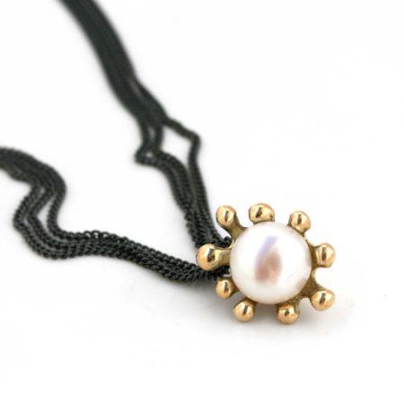 Søanemone halskæde i guld med hvid perle, her set liggende. Håndlavet af Christel Kaaber Guldsmedie