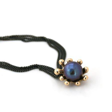 Søanemone halskæde i 14 kt guld med mørk perle her set liggende. Håndlavet af Christel Kaaber Guldsmedie