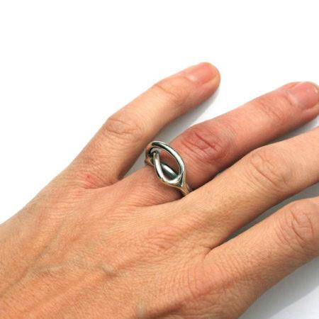 Designer ringe. Svingring i blankt sølv set på hånd. Håndlavet af Christel Kaaber Guldsmedie.