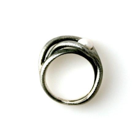 Fingerringe til kvinder. Svingring i sort sølv med hvid perle set i profil. Håndlavet af Christel Kaaber Guldsmedie