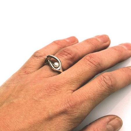 Fingerringe til kvinder. Svingring i sort sølv med en hvid perle set på hånden. Håndlavet af Christel Kaaber Guldsmedie.
